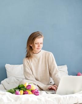 Gelukkig lachende vrouw zittend op het bed pyjama dragen, met plezier genieten van bloemen, werken op laptop