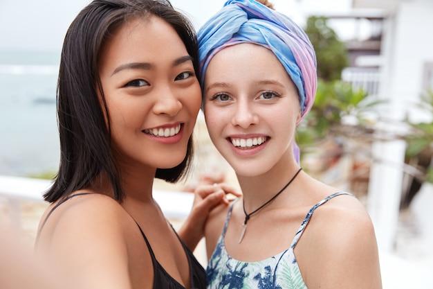 Gelukkig lachende vrouwtjes met vrolijke uitdrukkingen, hebben verschillende nationaliteiten en positieve looks.