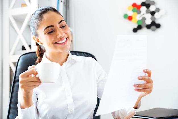 Gelukkig lachende zakenvrouw die documenten analyseert terwijl ze een koffiepauze op kantoor heeft