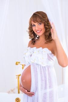 Gelukkig lachende zwangere vrouw in een witte jurk met orchideeën