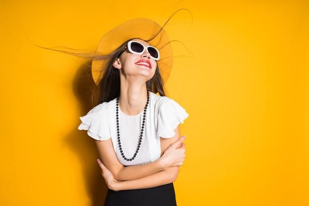 Gelukkig langharig meisje in zonnebril en hoed die zich voordeed op oranje achtergrond