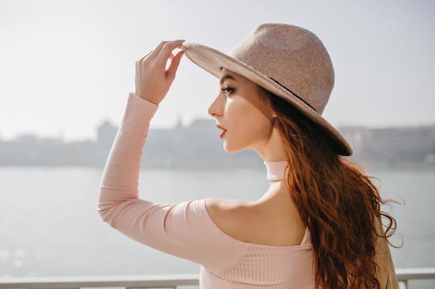 Gelukkig langharige brunette vrouw in roze kledij poseren op zeedijk