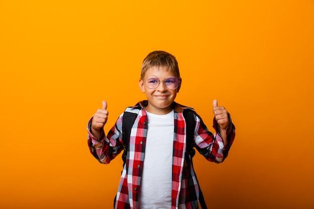 Gelukkig leerling toont klasse geïsoleerd op gele achtergrond.
