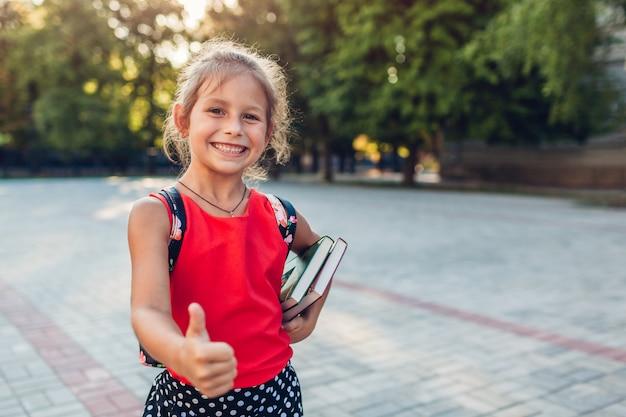 Gelukkig leerlingsmeisje dat rugzak draagt en boeken houdt