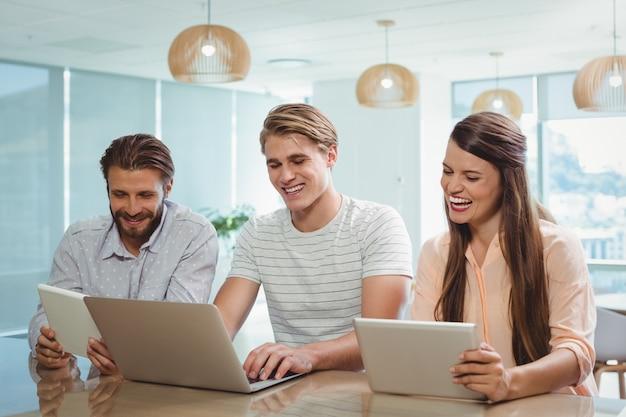 Gelukkig leidinggevenden met behulp van digitale tablet en laptop
