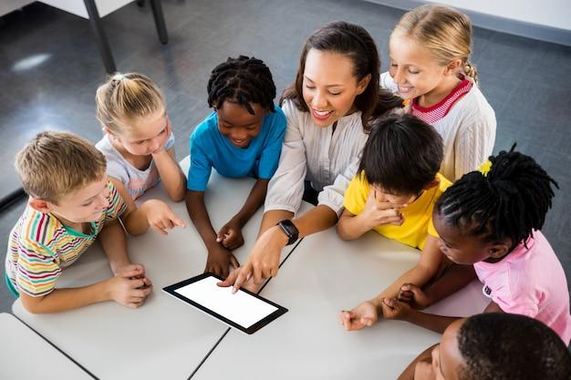 Gelukkig leraar en leerlingen met behulp van tablet pc