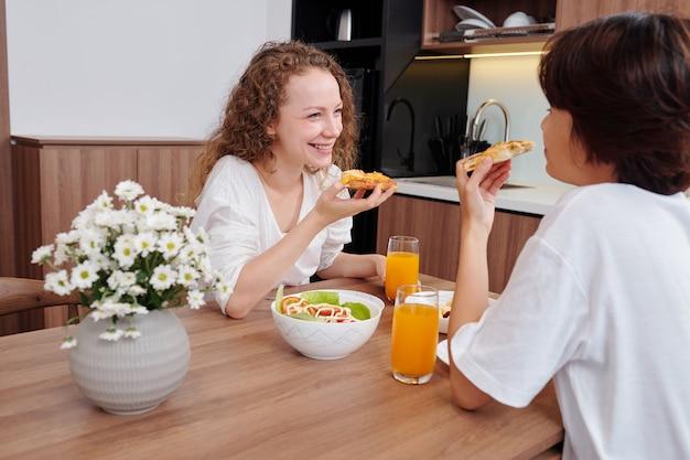 Gelukkig lesbisch koppel genieten van smakelijke pizza met salade en sinaasappelsap voor het avondeten, lachen en nieuws bespreken