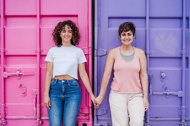 Gelukkig lesbisch koppel glimlachen, camera kijken en hand in hand over roze en paarse achtergrond. liefde is liefde. lgtbi-concept