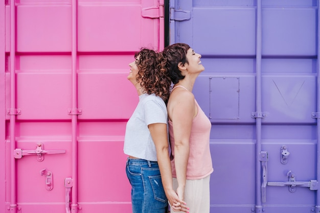 Gelukkig lesbisch koppel glimlachend en hand in hand over roze en paarse achtergrond. liefde is liefde. lgtbi-concept