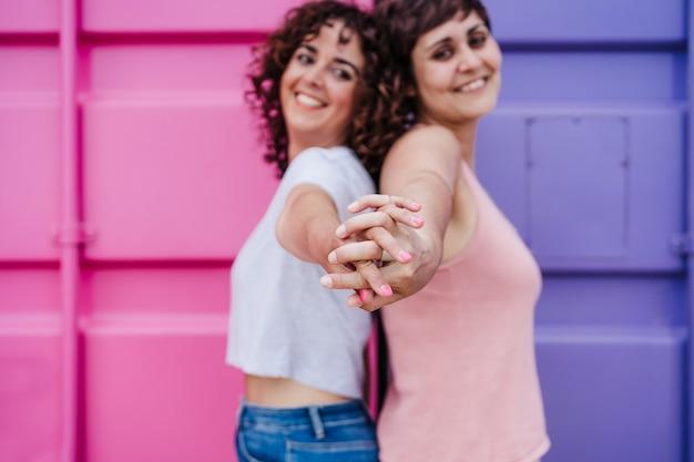 Gelukkig lesbisch koppel hand in hand over roze en paarse achtergrond. selectieve focus op handen. liefde is liefde. lgtbi-concept