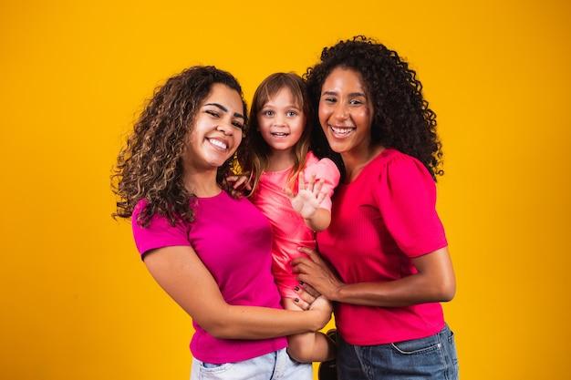 Gelukkig lesbisch koppel met geadopteerd meisje op kleur achtergrond