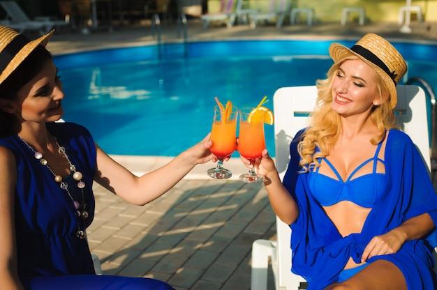 Gelukkig leuke jonge vrouwen met cocktails lachen en plezier in de buurt van zwembad.