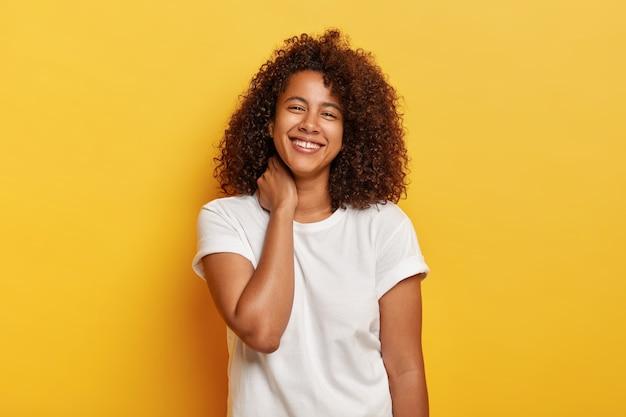 Gelukkig levensstijlconcept. aangenaam uitziende grappige afro-vrouw voelt zich gelukkig en tevreden, lacht vrolijk, heeft witte tanden met een kleine opening, geniet van een geweldige vrije dag, staat tegen een gele muur