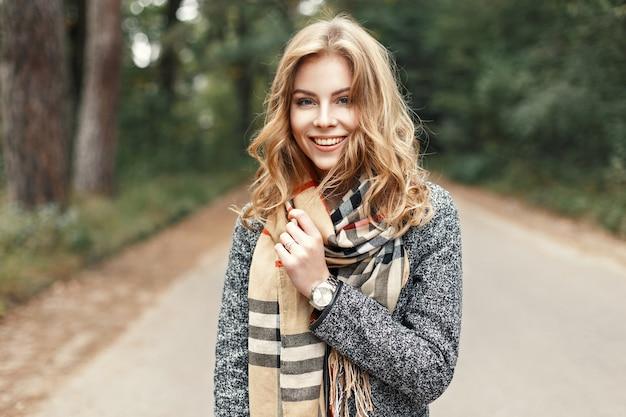 Gelukkig levensstijlportret van een mooi jong modelmeisje met een lieve glimlach in een warme herfstsjaal.