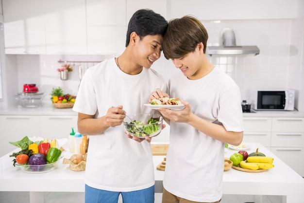 Gelukkig lgbt aziatisch jong stel houdt salade en sandwich vast om te eten na het koken in de keuken. lieve homomannen. gezonde levensstijl voor homoseksuele familie van hetzelfde geslacht in het weekend.
