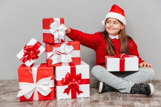 Gelukkig lief klein meisje in de hoed van de kerstman die de huidige doos neemt