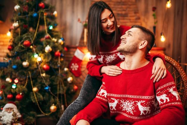 Gelukkig liefdepaar viert kerstvakantie. kerstviering, vrolijke man en vrouw samen, dennenboom met decoratie
