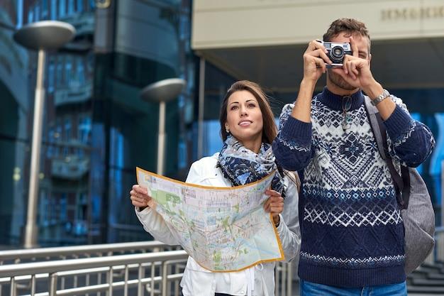 Gelukkig liefdespaar toeristen die foto's nemen op excursie of stadstour. reis samen met een kaart en retro camera