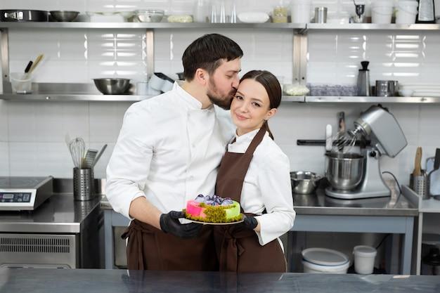Gelukkig liefdevol paar banketbakkers, een man en een vrouw houden een moussecake in hun handen