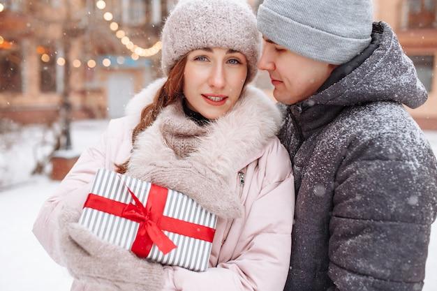Gelukkig liefdevol paar buiten in het winter besneeuwde park met een cadeautje met rood lint in handen. vrolijke man en vrouw die valentijnsdag samen vieren. datum op een koude winterdag buiten.