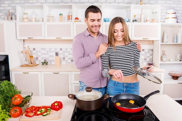 Gelukkig liefdevol paar koken in de keuken en zoute omelet
