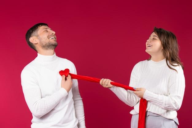 Gelukkig liefdevol paar op een rode achtergrond. het meisje scheurt een hart uit de borst van de man. valentijnsdag concept.