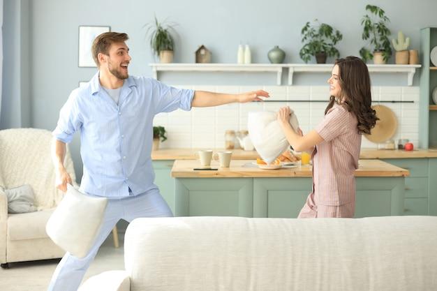 Gelukkig liefdevol stel dat plezier heeft tijdens een kussengevecht in de woonkamer.