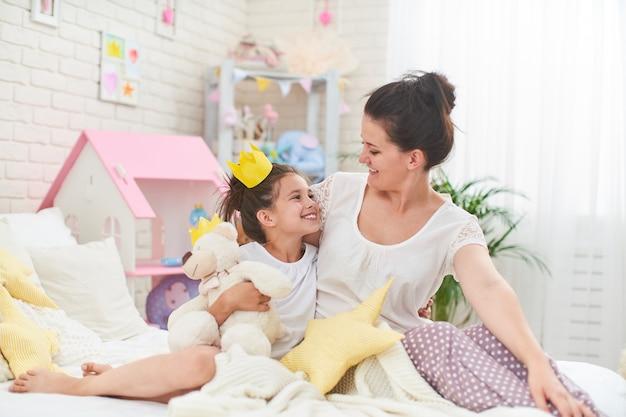 Gelukkig liefdevolle familie. ãƒâƒã'â ãƒâ'ã'âœãƒâƒã'â ãƒâ'ã'â¾ãƒâƒã'â ãƒâ'ã'â¼ en dochter spelen in kronen en knuffelen op bed.