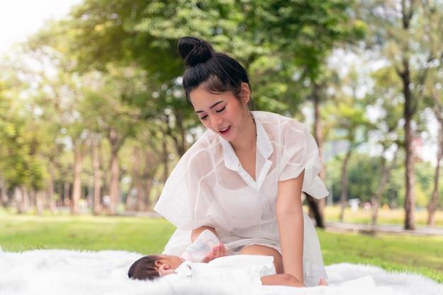 Gelukkig liefdevolle familie. aziatische jonge mooie moeder en haar pasgeboren kind zachtjes aan te raken en zuigfles met liefde op groen gras in het park te voeden