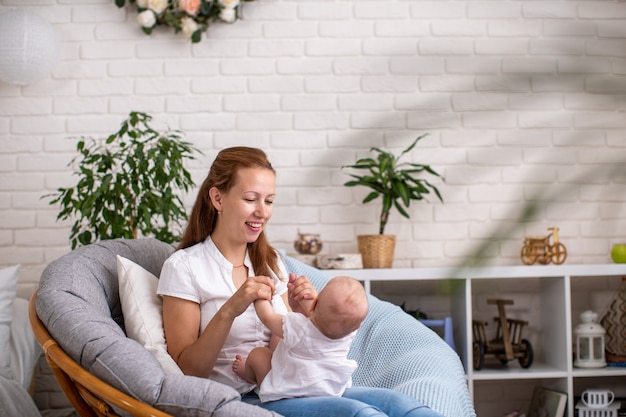Gelukkig liefdevolle familie. een jonge moeder speelt met haar kind in de slaapkamer.