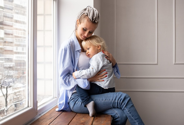 Gelukkig liefdevolle familie. hipster moeder en haar zoon kind jongen spelen en knuffelen.