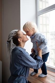 Gelukkig liefdevolle familie, moeder en babyjongen kussen en spelen