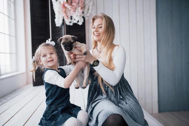 Gelukkig liefdevolle familie. moeder en haar dochter kind meisje spelen en knuffelen schattig pug