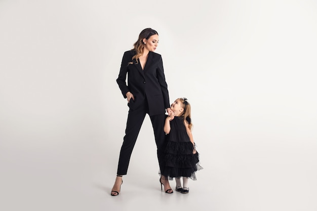 Gelukkig liefdevolle familie. moeder en haar dochterkindmeisje op een grijze achtergrond