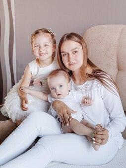 Gelukkig liefdevolle familie. moeder en haar dochters kinderen meisjes spelen, zitten op de bank en knuffelen
