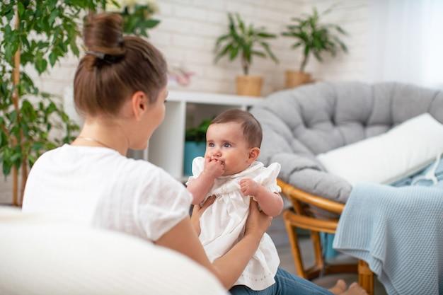 Gelukkig liefdevolle jonge moeder spelen met haar baby in de slaapkamer