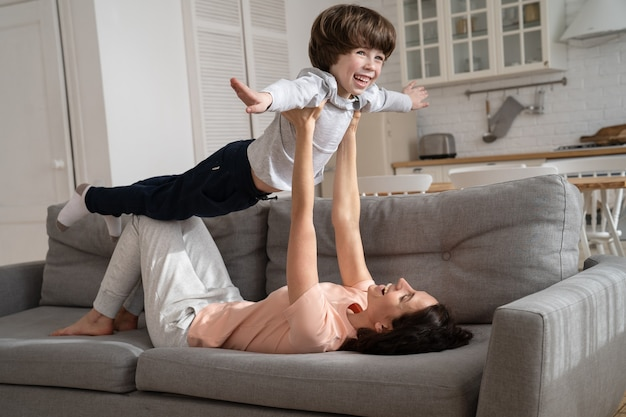Gelukkig liefdevolle moeder spelen met schattige zoon