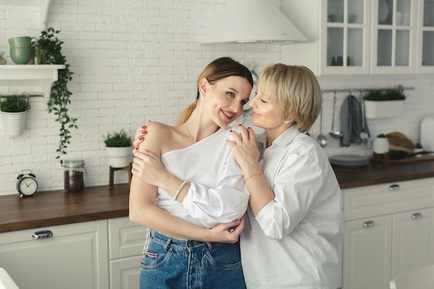 Gelukkig liefdevolle oudere rijpe moeder en volwassen dochter lachen omarmen