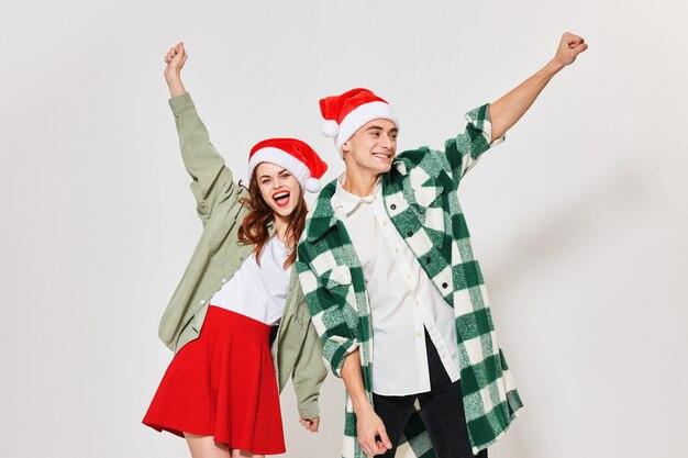 Gelukkig liefdevolle paar gebaren met hun handen op een lichte ruimte en een kerstmuts op hun hoofd.