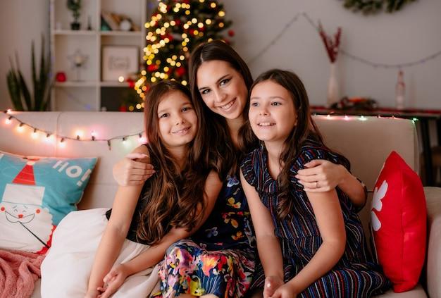 Gelukkig liefdevolle twee zussen en jonge moeder thuis in de kersttijd zittend op de bank in de woonkamer moeder knuffelen dochters oudste dochter kant kijken jongere en moeder camera kijken