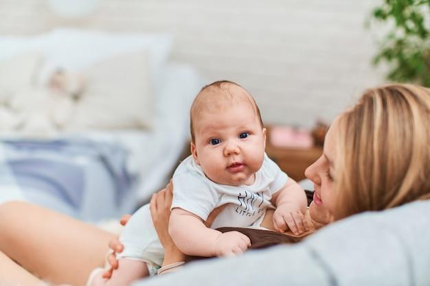 Gelukkig liefhebbende moeder zit op de sofa met zoontje