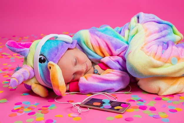Gelukkig luistert weinig blondemeisje in eenhoornkigurumi naar muziek die in hand smartphone op een roze oppervlakte houdt