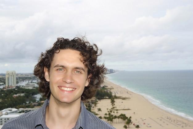 Gelukkig macho en zee strand. man die lacht met krullend donkerbruin haar op zeegezicht achtergrond in fort lauderdale, verenigde staten. toerisme en toeristische bestemming. zomervakantie en reizen concept