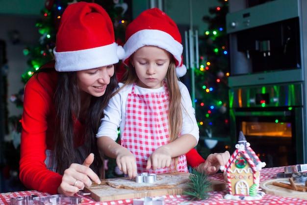 Gelukkig mamma en meisje in kerstman hoed peperkoek kerstkoekjes samen bakken