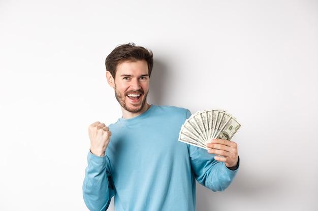 Gelukkig man dansen met geld, dollars tonen en ja zeggen met tevreden glimlach, vuist pomp gebaar maken, staande op witte achtergrond.