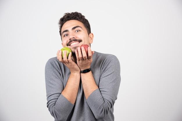 Gelukkig man die lacht met appels op grijs.