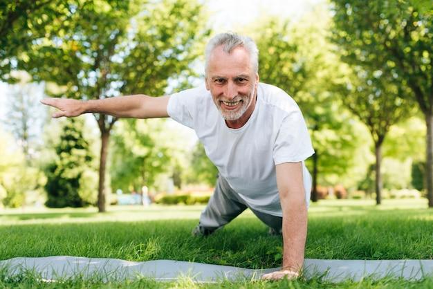 Gelukkig man doet push-ups in de natuur