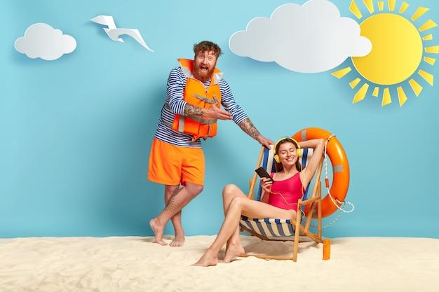 Gelukkig man draagt zeeman trui en reddingsvest, staat in de buurt van een strandstoel waar ontspannen vrouw muziek in koptelefoon luistert