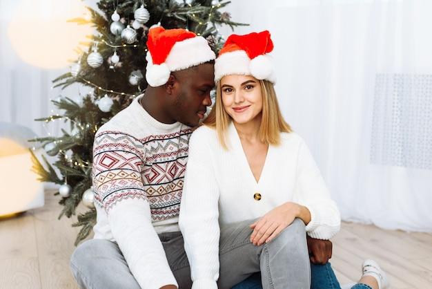 Gelukkig man en vrouw genieten van wintervakantie feest in de buurt van ingerichte dennenboom.