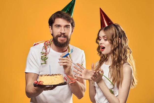 Gelukkig man en vrouw in een pet die een verjaardag vieren op een geel
